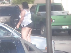 Plus-size Latina washing car..